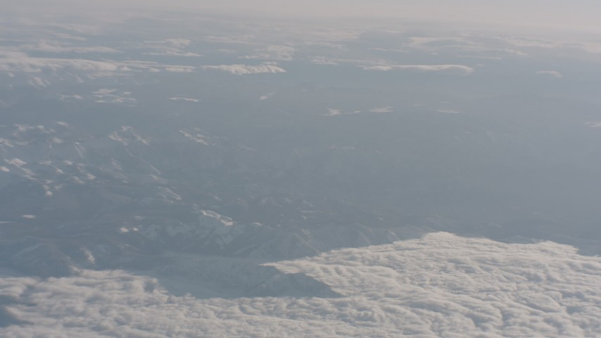 4K stock footage aerial video pan across snowy mountains and clouds in the Sierra Nevada Mountains, California Aerial Stock Footage | WA002_034