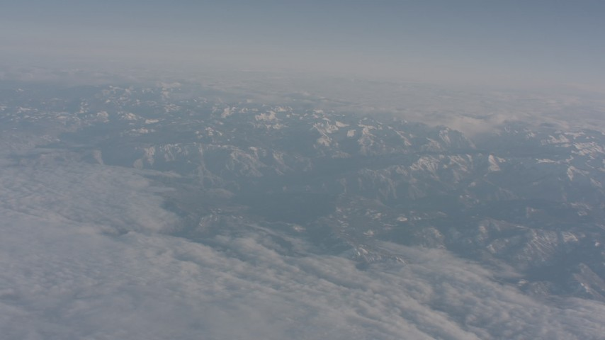 4K stock footage aerial video tilt from a bird's eye of clouds to reveal snowy Sierra Nevada Mountains, California Aerial Stock Footage | WA002_036