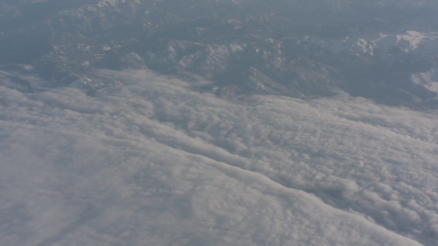 Pan across Sierra Nevada Mountains and a dense layer of clouds, California Aerial Stock Footage | WA002_037
