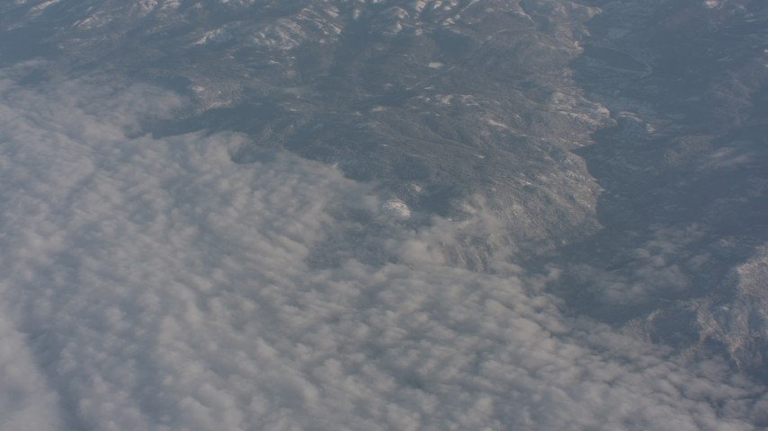 4K stock footage aerial video of the edge of cloud layer beside Sierra Nevada Mountains, California Aerial Stock Footage | WA002_041