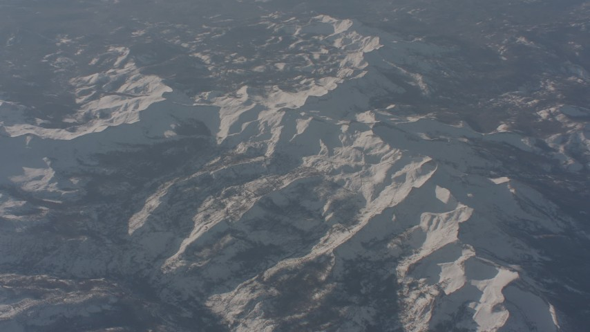 4K stock footage aerial video of a reverse view of snow-covered ridges in the Sierra Nevada Mountains, California Aerial Stock Footage | WA002_055