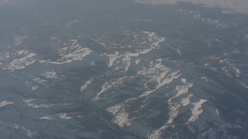 4K stock footage aerial video fly away from snow-covered ridges in the Sierra Nevada Mountains, California Aerial Stock Footage | WA002_056