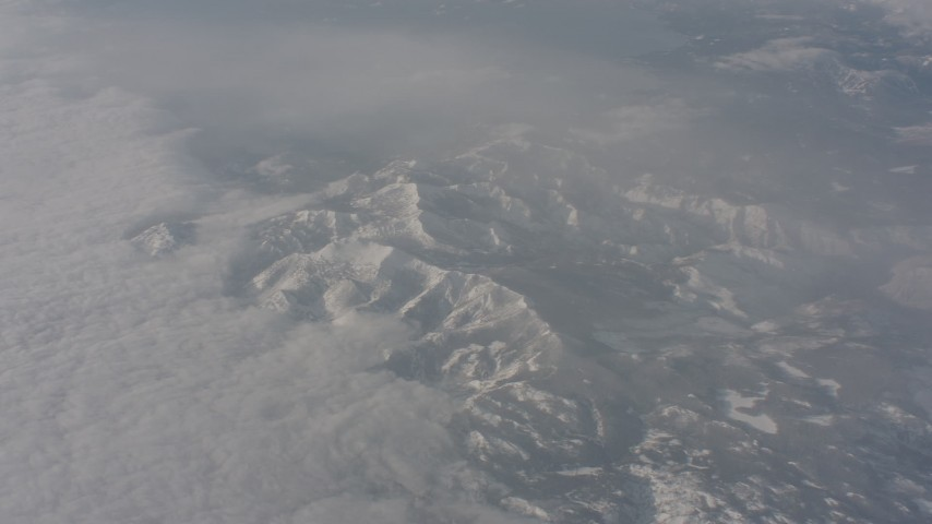 Sierra Nevada Mountains below misty clouds, California Aerial Stock Footage | WA002_075