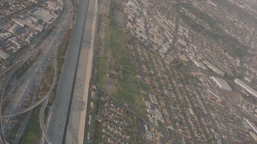 Pan across I-105 and I-710 interchange by Los Angeles River in Downey, reveal Lynwood suburbs, California Aerial Stock Footage WA003_023 | Axiom Images