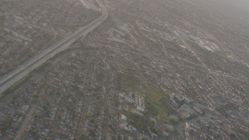Pan across neighborhoods to reveal I-105 with heavy traffic in Lynwood, California Aerial Stock Footage | WA003_024