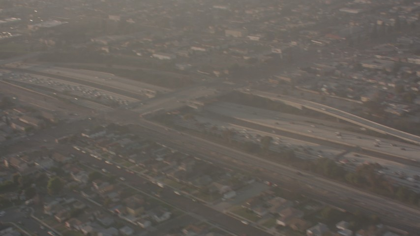 Pan across I-105 to reveal the Lear jet landing gear as the plane approaches Hawthorne Airport, California Aerial Stock Footage | WA003_026
