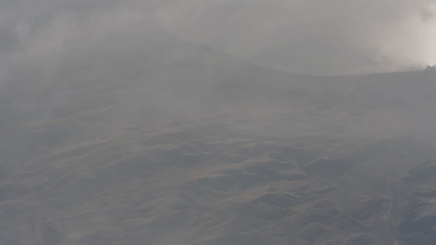 Reverse view of barren hills beside a lake in Northern California Aerial Stock Footage | WA004_002