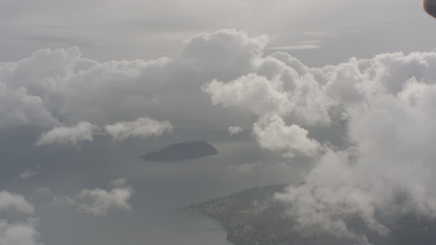 Flyby white clouds over a small island in Puget Sound in Washington Aerial Stock Footage | WA004_038