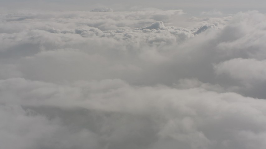 Tilt up while flying over a layer of clouds over Washington Aerial Stock Footage | WA004_046