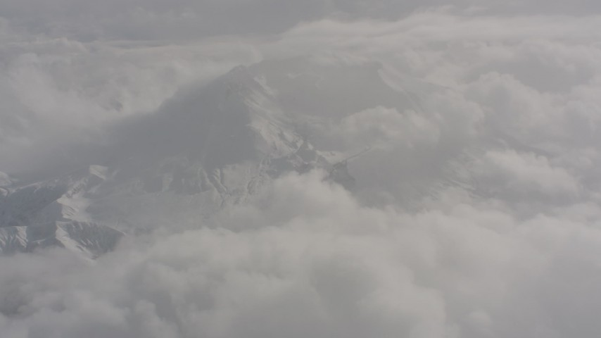 Fly over clouds to approach Mount St. Helens with snow in Washington Aerial Stock Footage | WA004_074