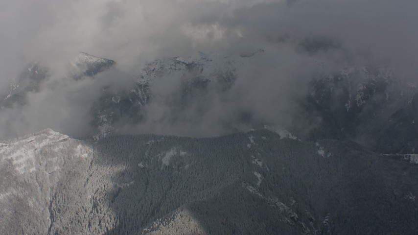 A bird's eye view of clouds, revealing snowy mountain ridges in Washington Aerial Stock Footage | WA004_080