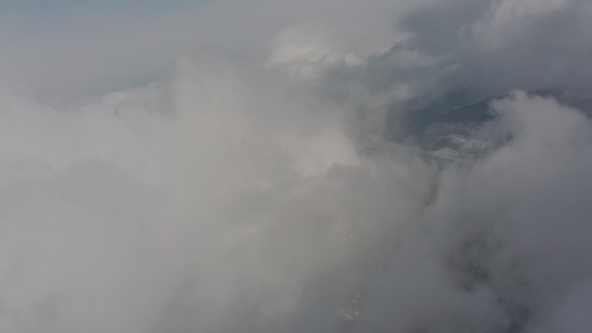 Tilting from snowy mountain ridges to approach clouds in Washington Aerial Stock Footage | WA004_081
