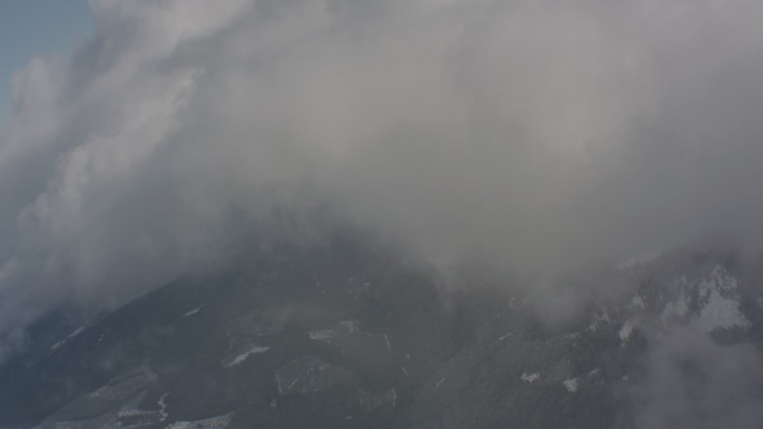 4K stock footage aerial video pan across clouds over snowy mountains, and approach a cloud bank in Washington Aerial Stock Footage | WA004_082