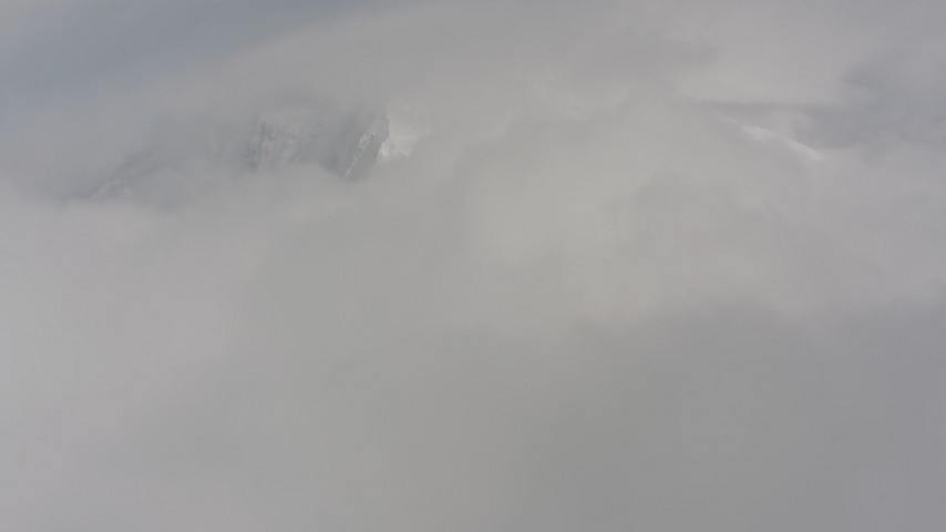 Fly over clouds toward a snowy mountain in the background, Washington Aerial Stock Footage | WA004_083
