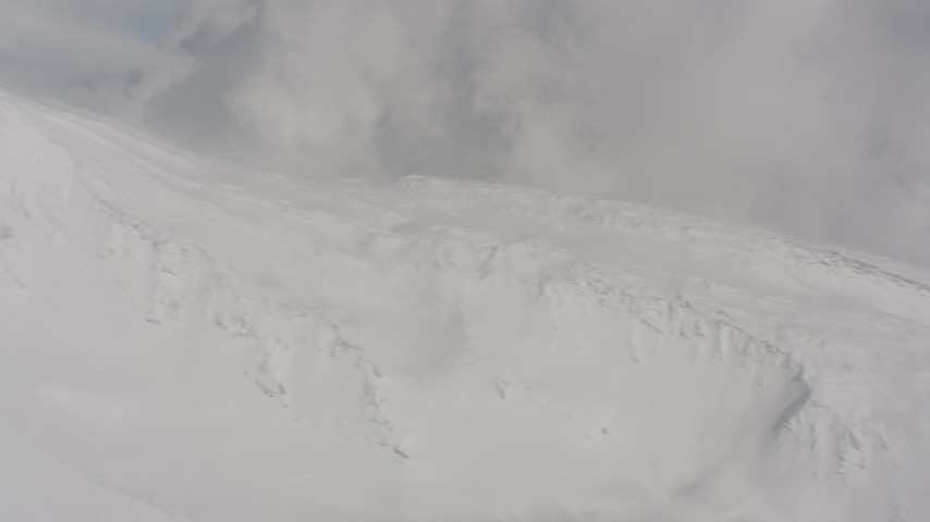 Pan across a snowy peak and clouds to a view of wilderness in Washington Aerial Stock Footage | WA004_085