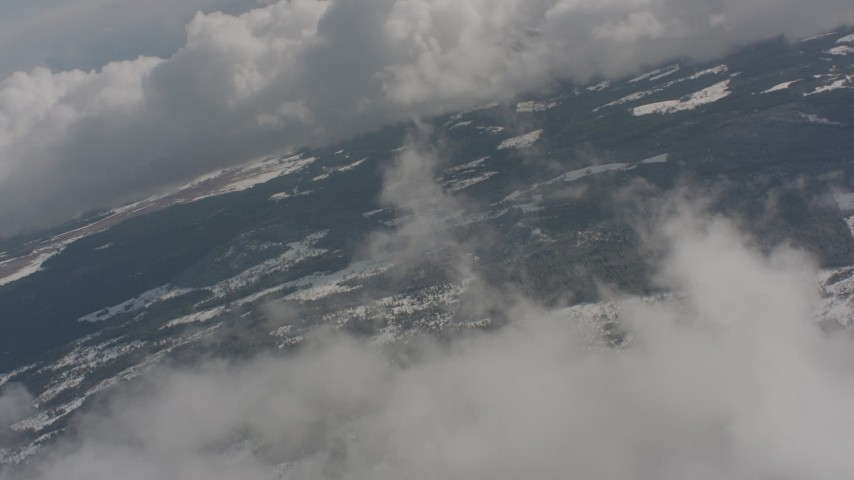Fly over clouds to approach snowy forests in Washington Aerial Stock Footage | WA004_088