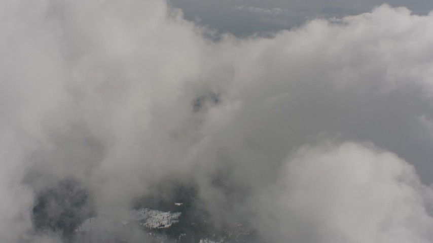 4K stock footage aerial video fly over clouds and snowy forest to approach a hole in the clouds, Washington Aerial Stock Footage | WA004_090
