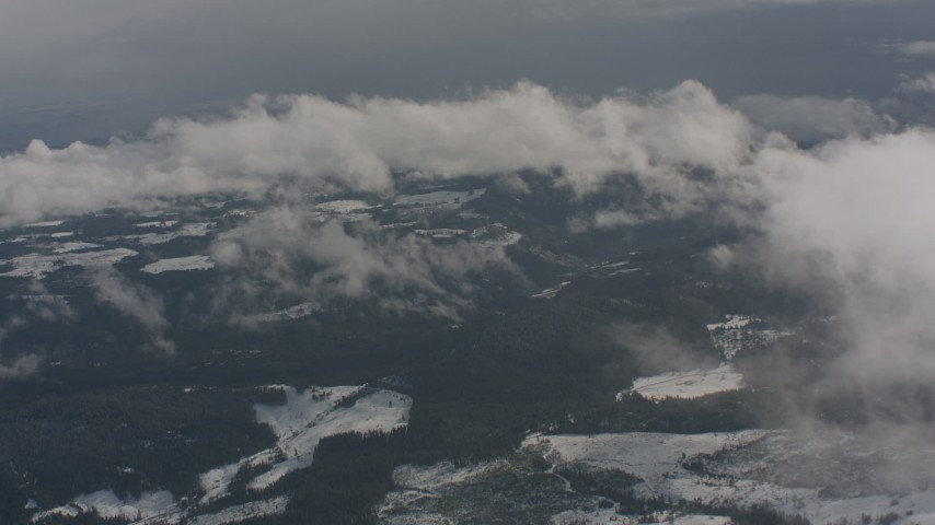 Fly over misty clouds to reveal evergreens and snow below in Washington Aerial Stock Footage | WA004_091