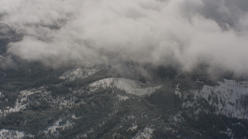 4K stock footage aerial video flyby clouds to reveal snow and forest below in Washington Aerial Stock Footage | WA004_092