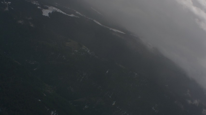 4K stock footage aerial video fly over clouds and reveal evergreen forests with snow in Washington Aerial Stock Footage | WA004_094
