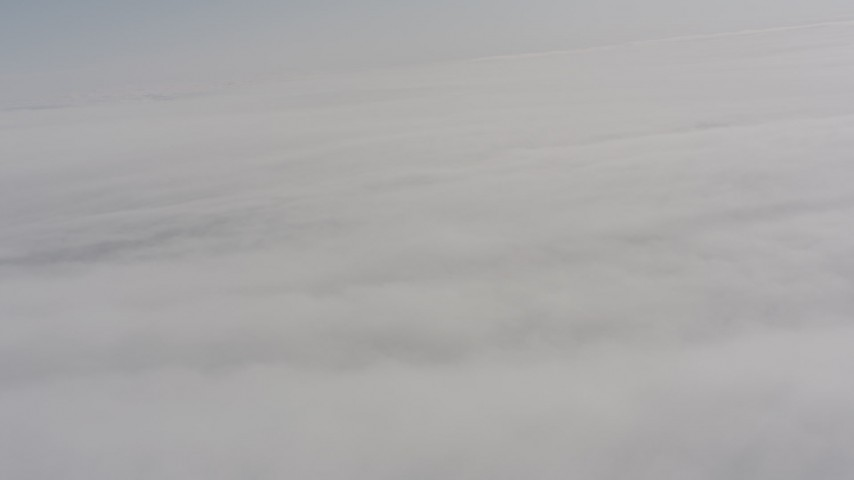 Tilt from a bird's eye view of clouds to a wider view of the cloud cover over Oregon Aerial Stock Footage | WA004_101
