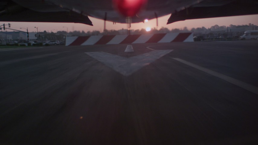 A reverse view of the runway while lifting off from Hawthorne Municipal Airport, California at sunset Aerial Stock Footage | WA005_001