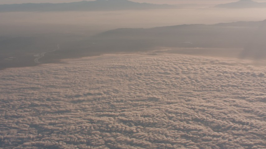Approach mountains at sunset, and tilt to clouds below in Southern California Aerial Stock Footage | WA005_012
