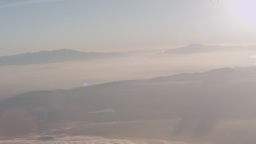 4K stock footage aerial video tilt from a bird's eye of clouds to reveal mountains at sunset in Southern California Aerial Stock Footage | WA005_013