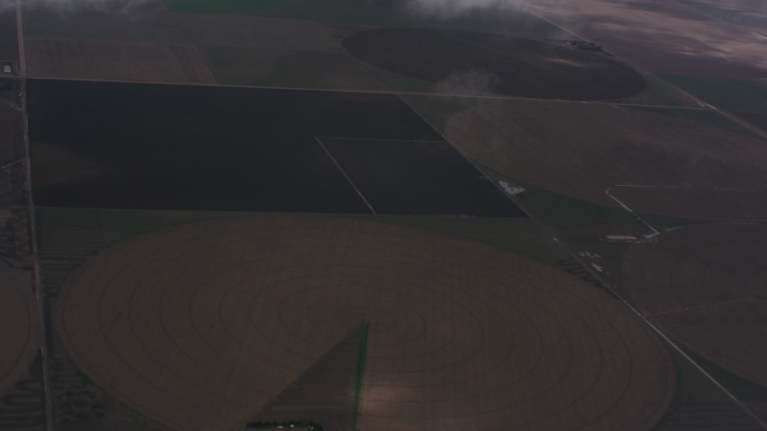 Fly through clouds to reveal farms and circular crop fields in Kansas Aerial Stock Footage WA005_027 | Axiom Images