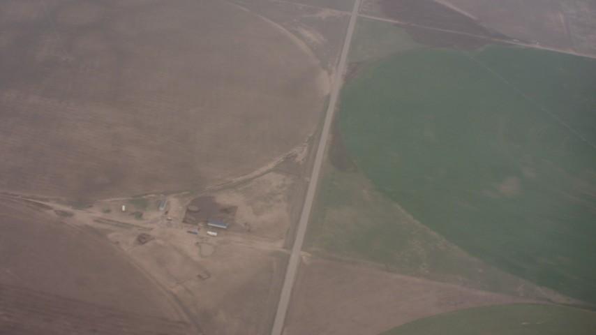 Reverse view of clouds revealing circular crop fields below in Kansas Aerial Stock Footage WA005_030 | Axiom Images
