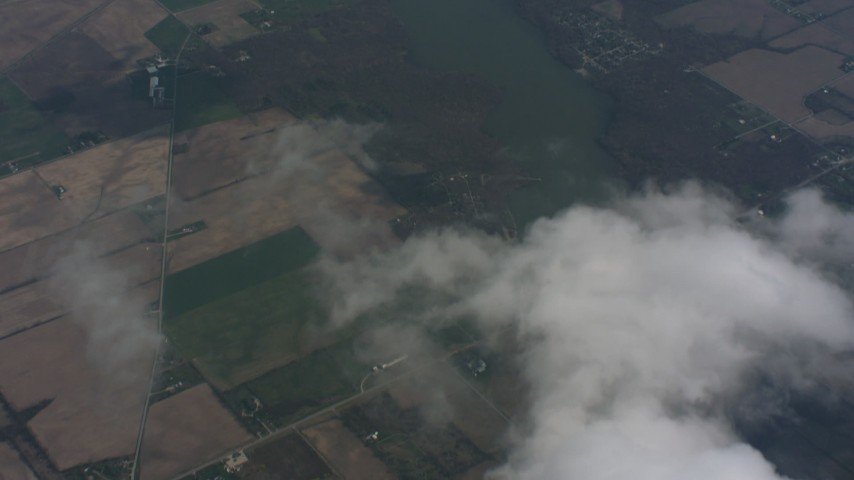 A bird's eye view of a cloud over Ohio farmland, tilt to reveal a lake Aerial Stock Footage | WA005_064