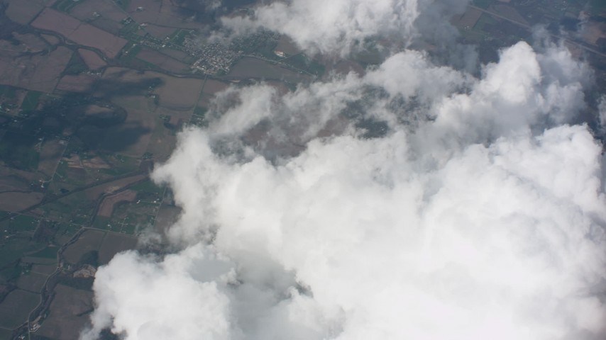 Tilt from larger cloud formations to smaller clouds over Ohio farmland Aerial Stock Footage | WA005_082