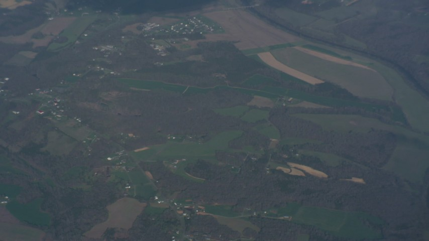 Tilting from a bird's eye of farm fields to reveal clouds above Virginia Aerial Stock Footage | WA006_004