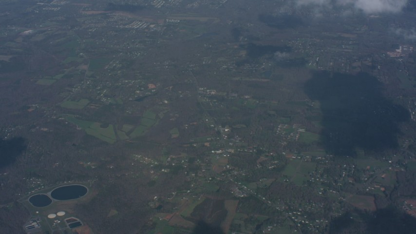 Tilt to a cloud over rural Virginia, and tilt up to a wider view of small clouds over rural towns Aerial Stock Footage | WA006_005