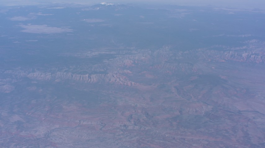 Tilt from desert mountains to reveal mesas and a distant peak in Arizona Aerial Stock Footage WA007_027 | Axiom Images
