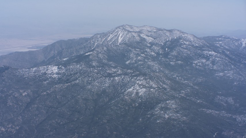 4K stock footage aerial video of a reverse view of snow-capped mountains, tilt to reveal a peak in Southern California Aerial Stock Footage | WA007_029