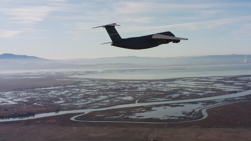 4K stock footage aerial video of a Lockheed C-5 flying over marshland in Northern California Aerial Stock Footage | WAAF01_C004_0117UU