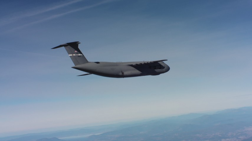 4K aerial video tilt to reveal a Lockheed C-5 flying over hills in Northern California Aerial Stock Footage | WAAF01_C012_0117G5