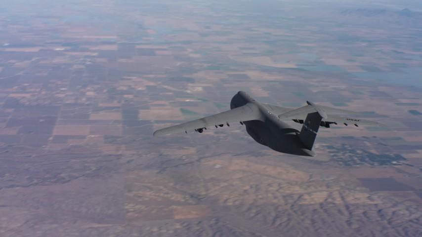 4K aerial video of tracking a Lockheed C-5 flying over hills near farmland in Northern California Aerial Stock Footage   WAAF01_C013_0117XK