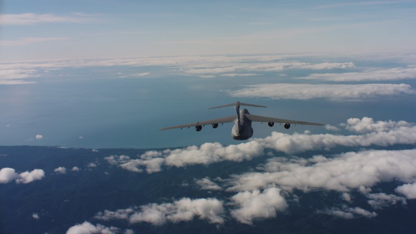 4K aerial video track Lockheed C-5 jet flying over mountains toward Pacific Ocean, Northern California Aerial Stock Footage | WAAF01_C038_011776