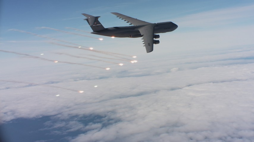4K stock footage aerial video of a Lockheed C-5 firing flares over clouds in Northern California Aerial Stock Footage | WAAF01_C048_0117DF