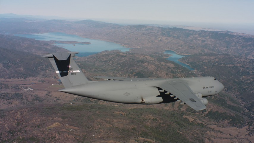 4K stock footage aerial video of a Lockheed C-5 flying over mountains near a lake, Northern California Aerial Stock Footage | WAAF01_C074_0117TM