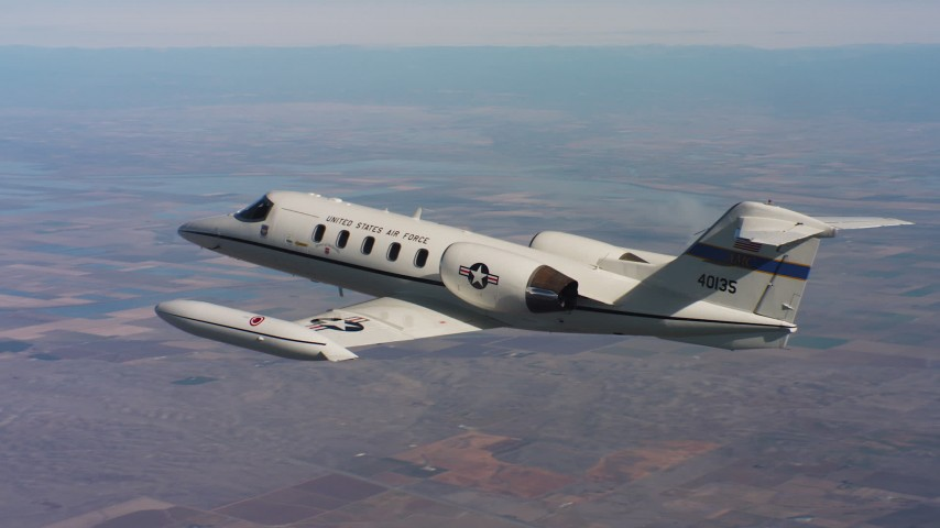 4K aerial video of revealing a Learjet C-21 as it descends into frame over farmland, Northern California Aerial Stock Footage | WAAF02_C010_011704