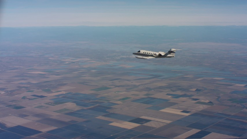4K aerial video of tracking a Learjet C-21 over farmland and leaving frame in Northern California Aerial Stock Footage | WAAF02_C012_01179Q