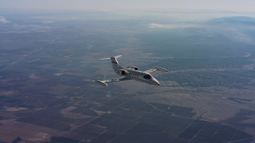 4K stock footage aerial video of flying around a Learjet C-21 in the air over farmland of Northern California Aerial Stock Footage | WAAF02_C015_01179B