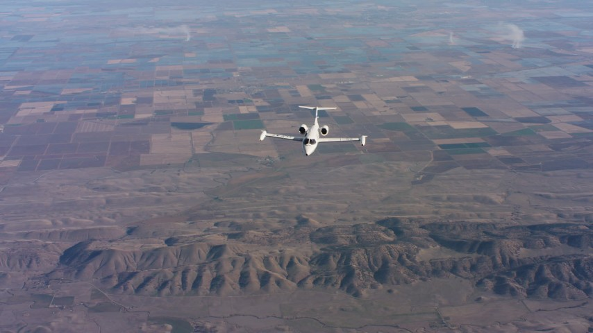 4K stock footage aerial video of reverse view of a Learjet C-21 flying over farm fields in Northern California Aerial Stock Footage | WAAF02_C017_0117TS