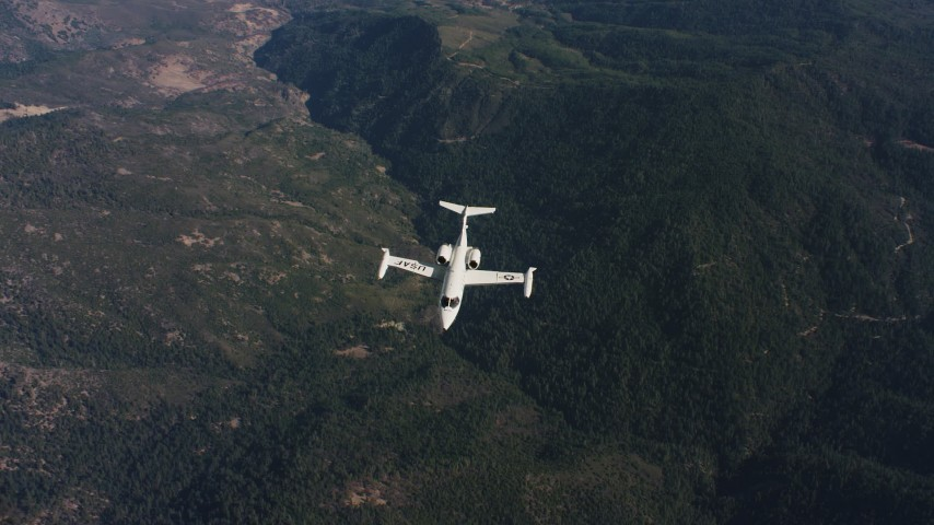 4K stock footage aerial video of a reverse view of mountains, revealing a Learjet C-21 in flight over Northern California  Aerial Stock Footage | WAAF02_C019_0117JN