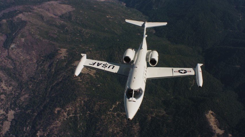 4K stock footage aerial video of a reverse view of a Learjet C-21 flying over mountains in Northern California Aerial Stock Footage | WAAF02_C019_0117JN_S000