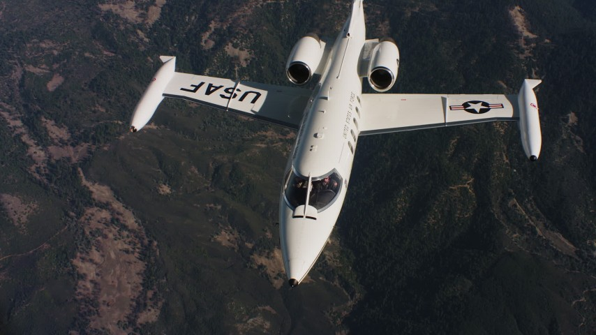 4K stock footage aerial video of a Learjet C-21 flying in and out of frame over mountains in Northern California Aerial Stock Footage | WAAF02_C019_0117JN_S001