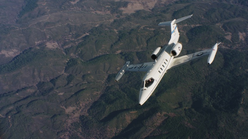 4K stock footage aerial video of a Learjet C-21 flying from side to side over mountains in Northern California Aerial Stock Footage | WAAF02_C019_0117JN_S002